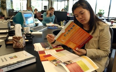 Tracy Yen looks over 401(k) documents at her office in Los Gatos, CA. After an experience with a previous employer, Yen opted to not participate in the 401(k) plan at her next job. (AP Photo/Ben Margot)