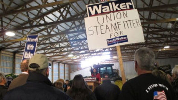 Retired union steamfitter Mike Reynders of Fort Atkinson, right, holds a sign in support of Wisconsin Gov. Scott Walker while listening to Lt. Gov. Rebecca Kleefisch speak Tuesday, April 10, 2012, in Dane, Wis (AP Photo/Scott Bauer)