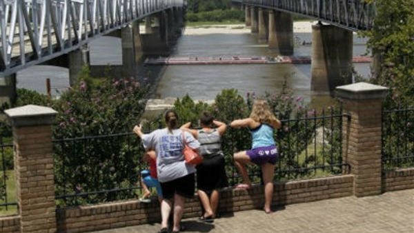 A family watches a barge pass along the Mississippi River in Vicksburg, Miss., the state with the highest obesity rate at 34.9 percent.  (AP Photo/Rogelio V. Solis)