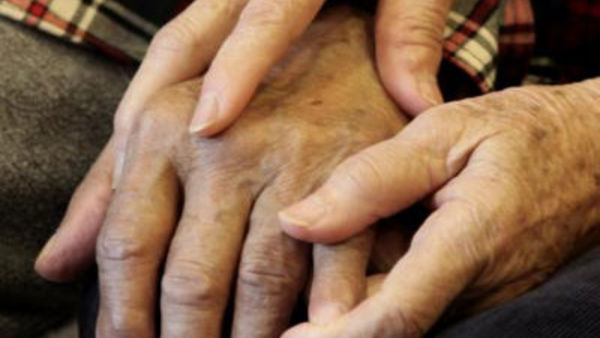 Shou-Mei Li holds the hand of her husband, Hsien-Wen Li, who is an Alzheimer's Patient. Ben Margot/Associated Press