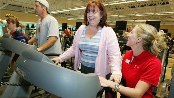 Wellness coach Julie Grosso, right, talks with Kelley Belkier as she works on a treadmill at a YMCA facility in Alapharetta, Ga. (AP Photo/RicFeld/File)