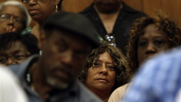 Vera Proctor, center, a retiree from the Detroit Police Department, listens to a news conference of union leaders in Detroit. (AP Photo/Paul Sancya)
