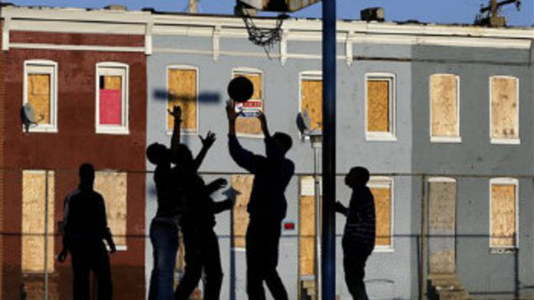 Children play basketball at a park near blighted row houses in Baltimore. (AP Photo/Patrick Semansky)