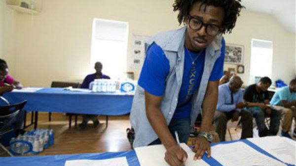 Americorps volunteer John Harris III, who is helping to coordinate a jobs fair program, aids job seekers in Washington.(AP Photo/Manuel Balce Ceneta, File)