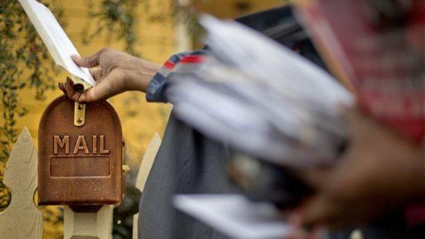 U.S. Postal Service letter carrier, Jamesa Euler, delivers mail, in Atlanta. (AP Photo/David Goldman, File)