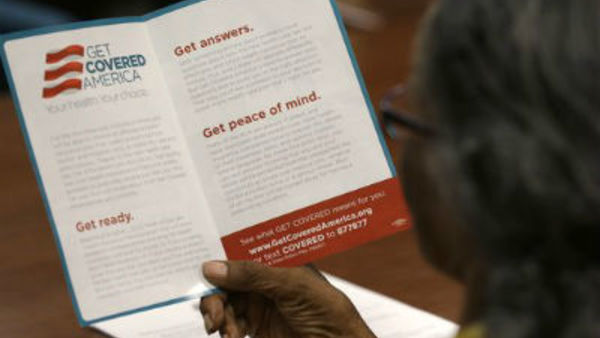 A consumer reads over a pamphlet about health care offerings under PPACA. (Photo: Wilfredo Lee, Associated Press)