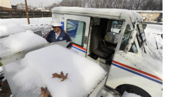 Postman Jim Doran delivers mail in Edgewood, Md. Monday, Dec. 9, 2013, after a winter storm dumped a mix of snow, freezing rain and sleet on the Mid-Atlantic region. (AP Photo/Steve Ruark)
