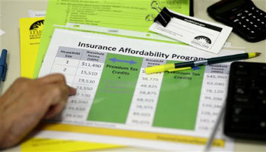 A volunteer counselor with Insure Central Texas uses a chart to help explain health insurance option, Tuesday, Oct. 1, 2013, in Austin, Texas. (AP Photo/Eric Gay)