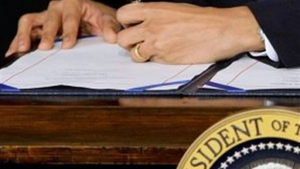 President Obama signs the Patient Protection and Affordable Care Act. (AP photo/J. Scott Applewhite)