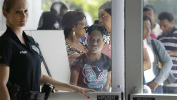 A police officer holds the door as people line up outside the Joe Celestin Center in North Miami, Fla., during National Youth Enrollment Day. (AP Photo/Wilfredo Lee)