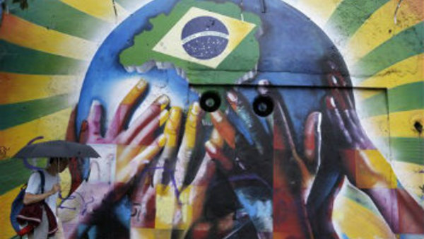A pedestrian passes a graffiti depicting human hands holding the earth with the Brazilian flag in Sao Paulo, Brazil, on Tuesday, June 10, 2014. (AP Photo/Thanassis Stavrakis)