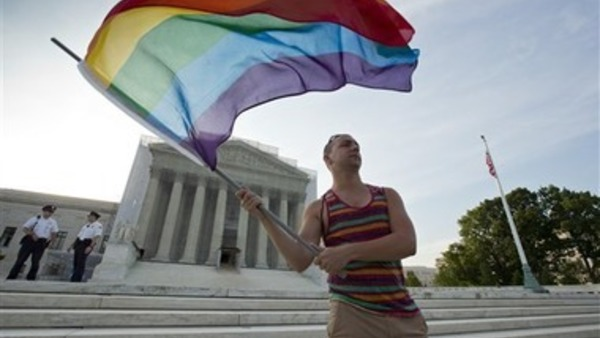 Gay rights advocate Vin Testa waves a rainbow flag in front of the Supreme Court. (AP Photo/J. Scott Applewhite)