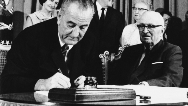 In this July 30, 1965 photo, President Lyndon Johnson signs the Medicare bill into law while former President Harry S. Truman, right, observes. Photo: AP.