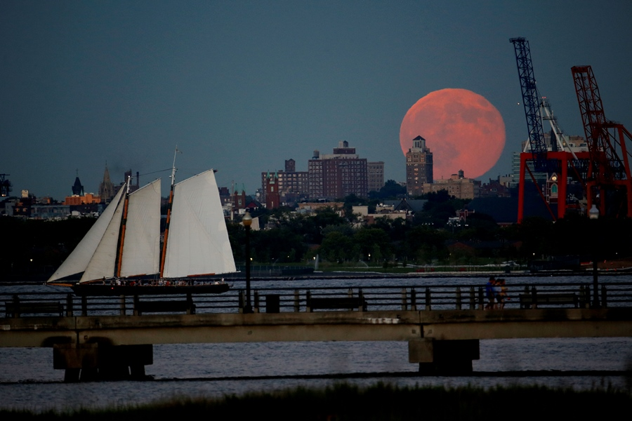 A blue moon rises behind Brooklyn seen from Liberty State Park in Jersey City, N.J., Friday, July 31, 2015. (AP Photo/Julio Cortez)