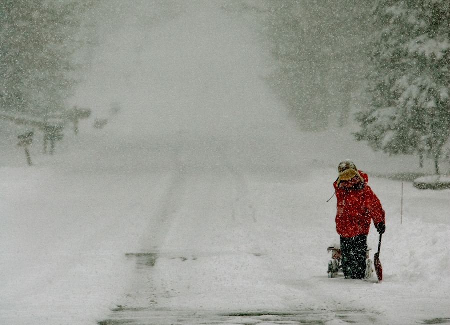 Child pulls a wagon full of snow in Brookfield, Wis. (AP Photo/Morry Gash)