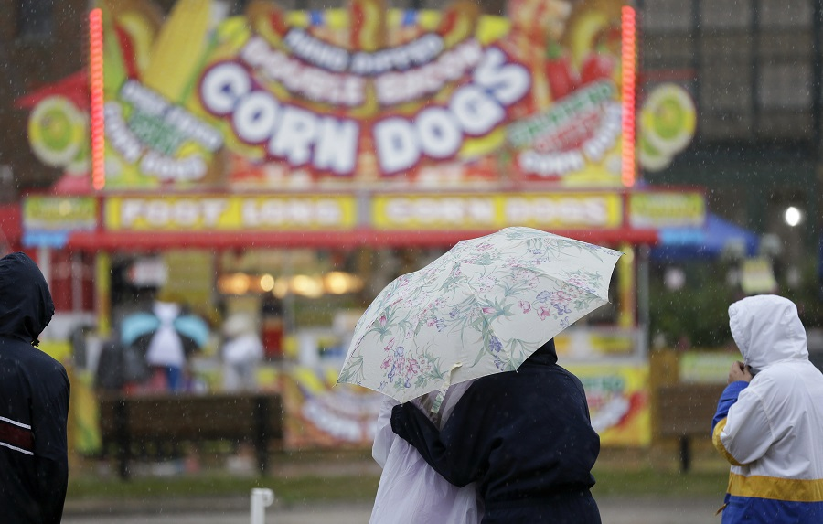 Fairgoers huddle under an umbrella during an afternoon rain shower at the Iowa State Fair, Tuesday, Aug. 18, 2015, in Des Moines, Iowa. (AP Photo/Charlie Neibergall)