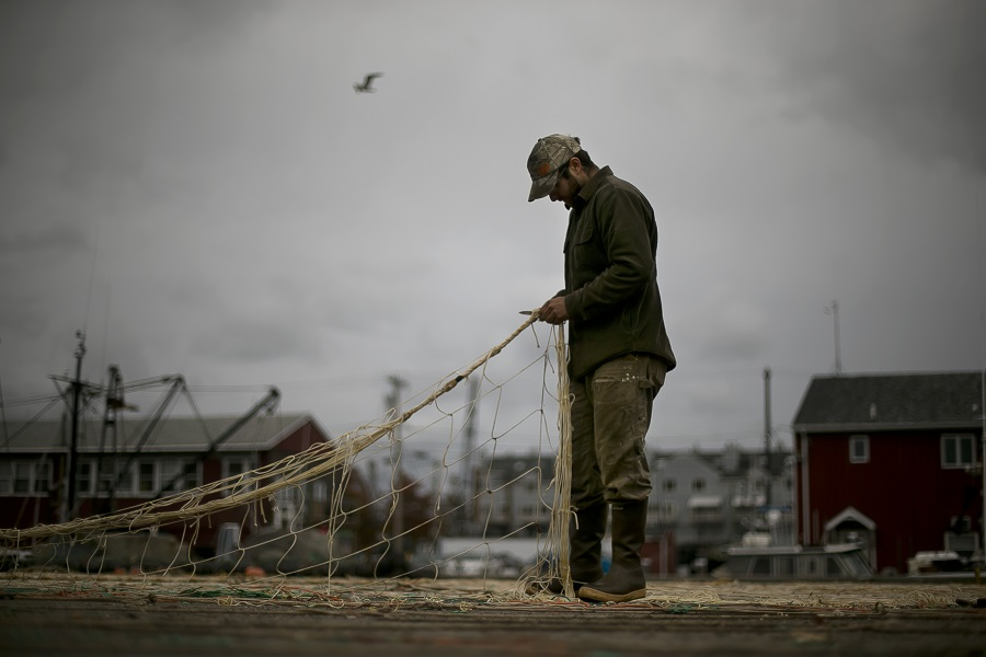 With stormy weather approaching, fisherman Brandon Wyman of Harpswell, Maine, repairs a trawling net, Wednesday, Oct. 28, 2015, in Portland, Maine. (AP Photo/Robert F. Bukaty)