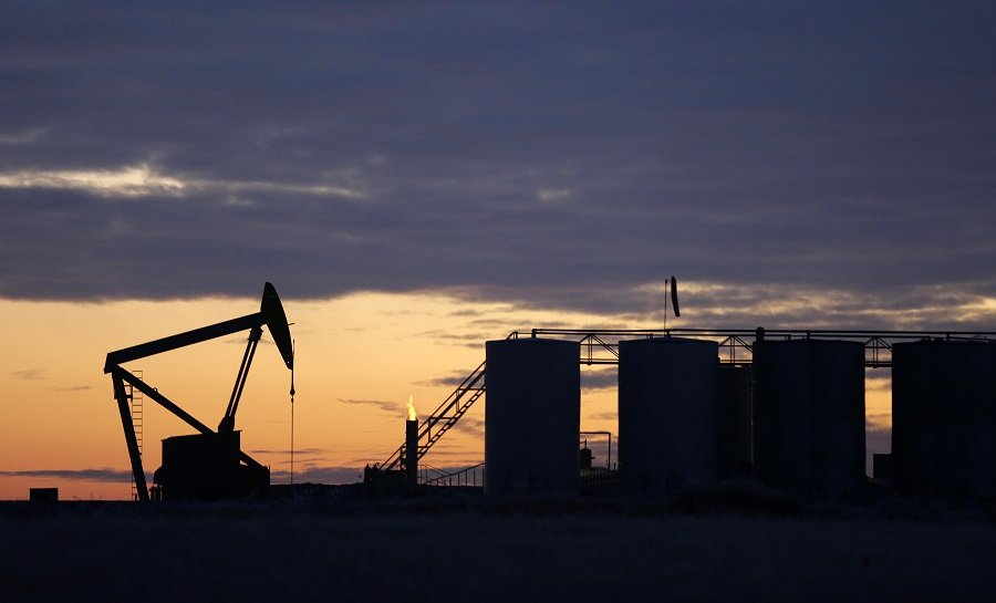 The sun begins to rise behind a pump jack and oil storage tanks, Friday, Dec. 19, 2014, near Williston, N.D. (AP Photo/Eric Gay)