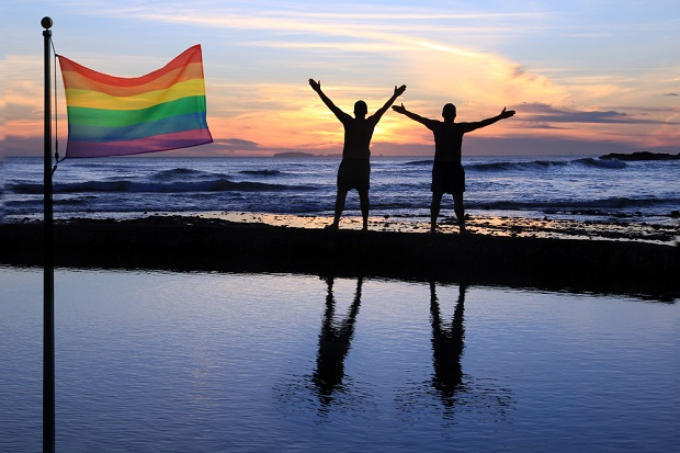 two people by ocean with rainbow flag