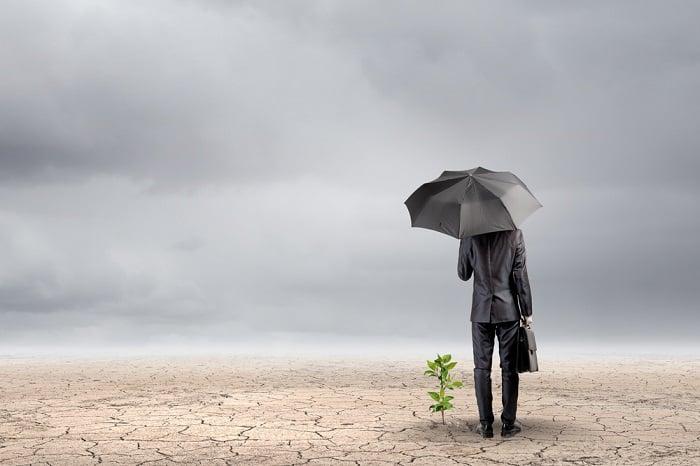 Man with umbrella in desert