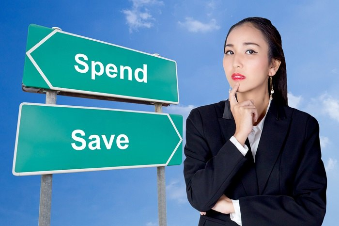 Woman considering save or spend sign