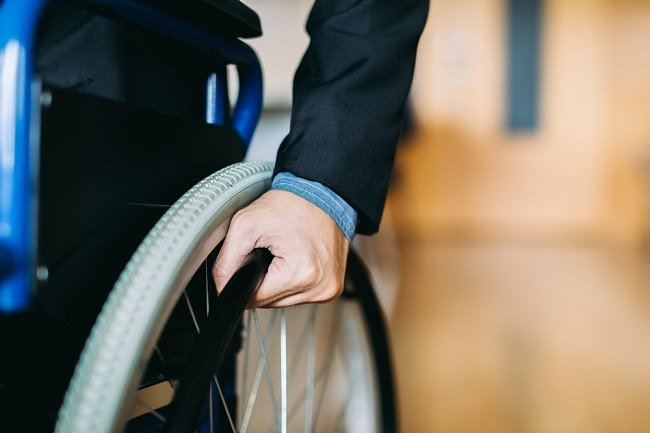 man with hand on wheelchair wheel