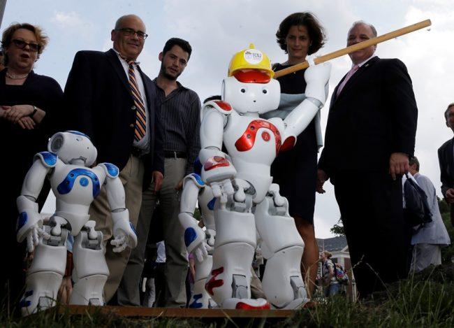 People standing around robots.