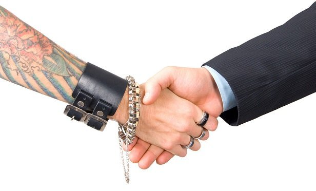 Tattooed person shaking hands with businessman