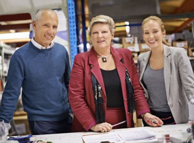 Older man and woman at work with younger woman