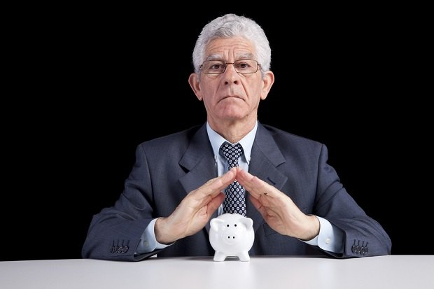 older business man with hands over piggy bank