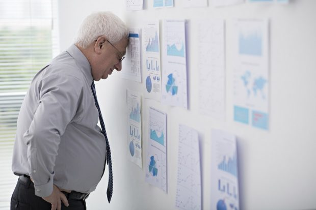 older man with forehead against wall
