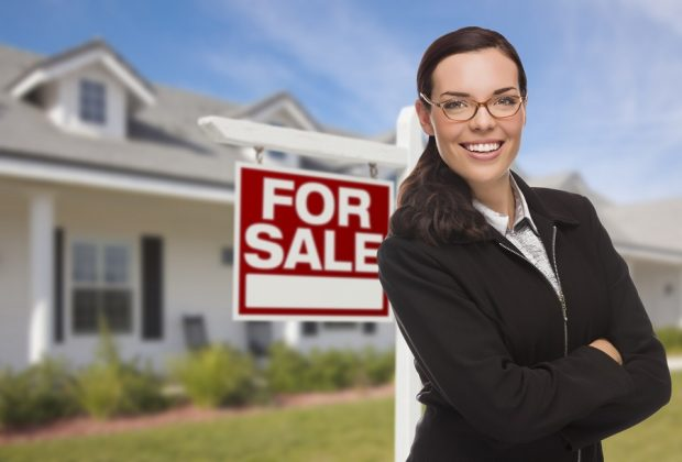 realtor in front of for sale sign