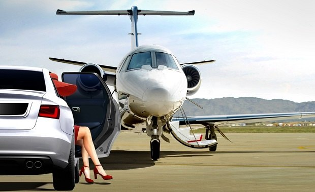 woman sitting in car next to private jet