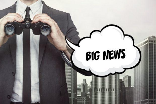 man with binoculars and sign saying big news