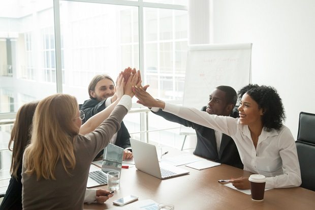Team of employees high-fiving