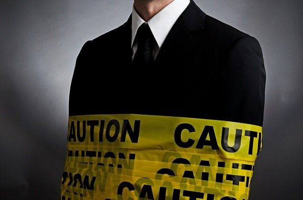 Business man wrapped in yellow caution tape