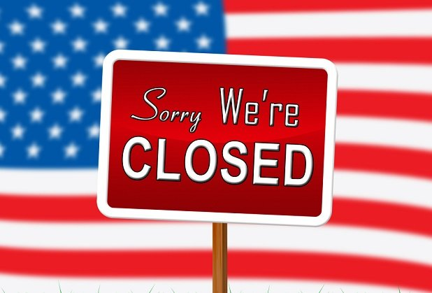 U.S. flag with sign saying Closed
