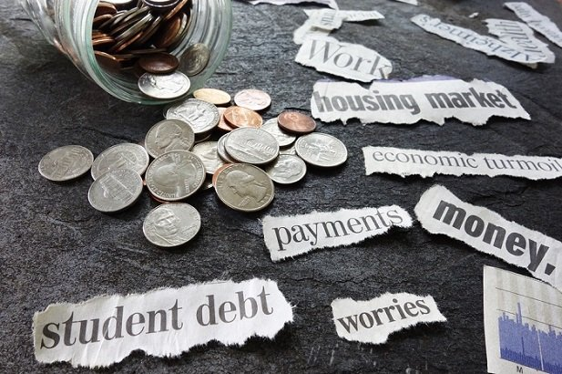 coins spilling from jar and word student debt