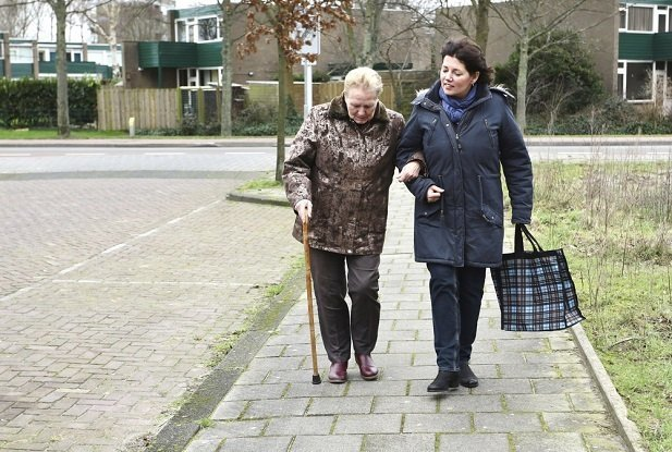 Woman helping older woman walk