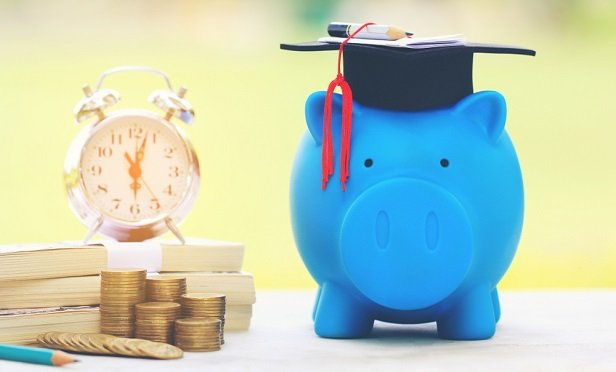 Piggy bank in graduation cap next to stacks of coins