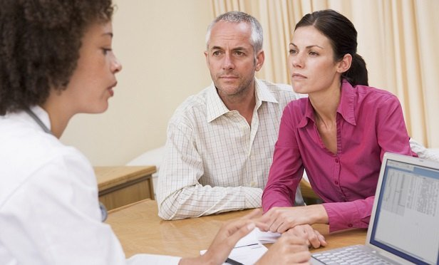 Man and woman speaking with doctor