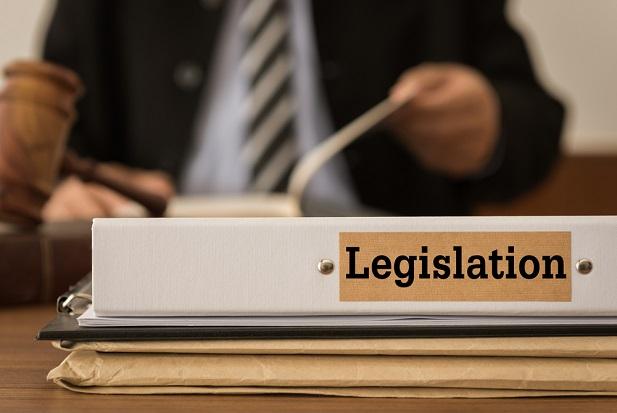 Notebook saying Legislation before man at desk