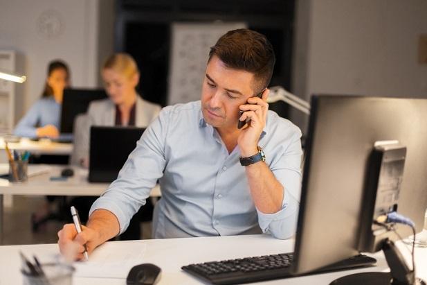 man on phone taking notes