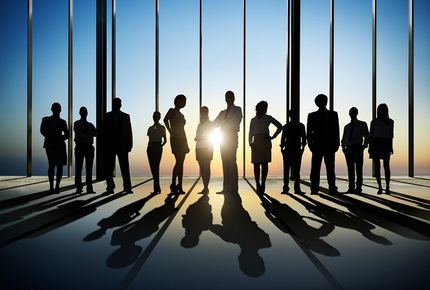 business people silhouetted against light