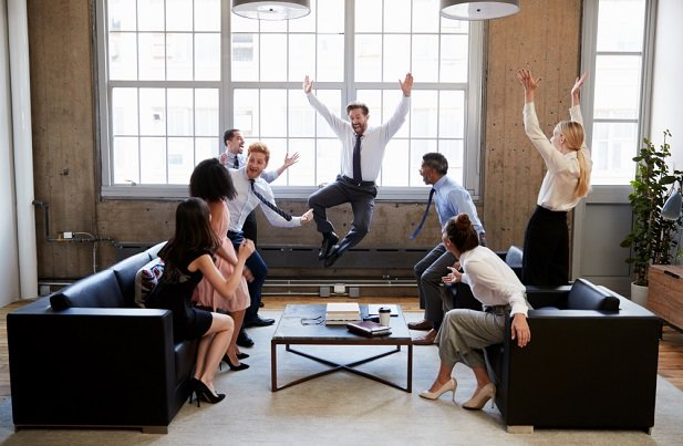 man in office jumping for joy