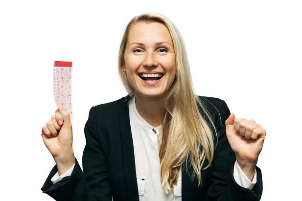 happy woman waving lottery ticket