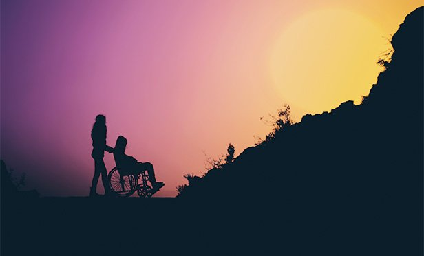 Silhouette of person pushing wheelchair up hill