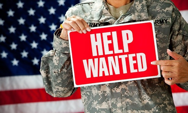 Military person holding help wanted sign