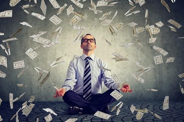 man meditating in shower of dollars
