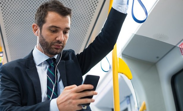 Businessman checking phone on train